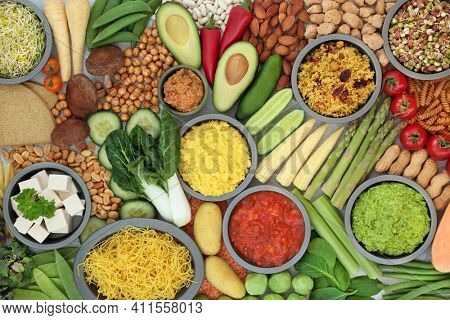 Healthy vegan food for vitality and fitness with bean curd, vegetables, legumes, nuts, dips, grains, oatmeal crackers and pasta. Health foods that lower cholesterol and blood pressure. Top view.