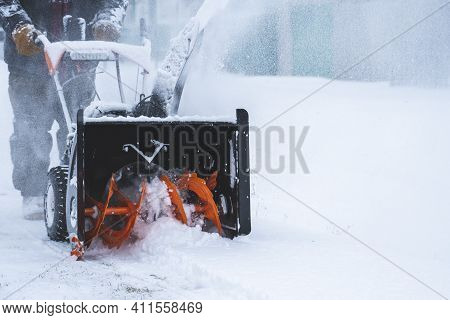 A Man Removes Snow With A Snow Plow After A Heavy Snowfall Near His House, Close-up, Blizzard, Snow