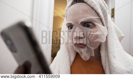 Portrait Of A Young Girl With A Towel On Her Head And A Fabric Face Mask On Her Head Looking At Smar