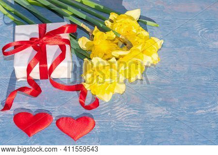 Yellow Bright Daffodils, A White Gift Box With A Red Ribbon And Two Red Hearts On A Blue Wooden Back