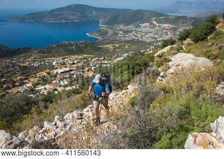 Hiking Lycian way. Man is trekking on stony path high above Mediterranean sea coast on Lycian Way trail near Kalkan, Outdoor activity in Turkey