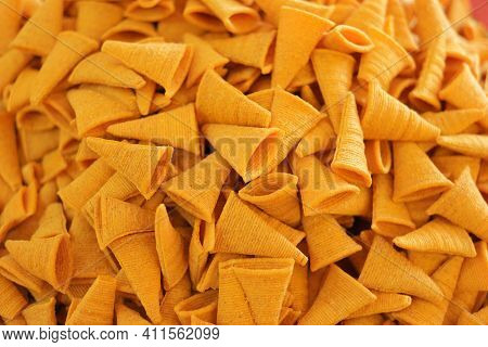 Triangle Crunchy Corn Cheese Flavor Snack Background. Background Of Crispy Corn Snack.