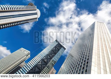 Tokyo skyscrapers with blue sky and clouds. Modern architecture detail with space for text. Tokyo city financial district, Japan.