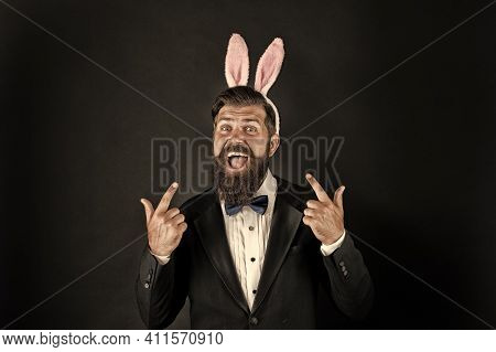 Easter Idea. Happy Manager Pointing Fingers Up. Bearded Man With Bunny Ears Pointing Black Backgroun