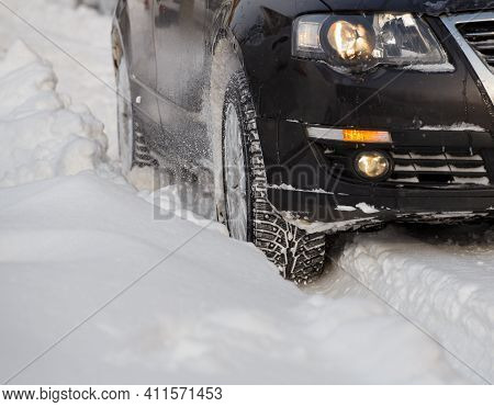 Black Vehicle Moving Through The Deep Snow Skidding, Cars Wheel Spin And Spew Up Pieces Of Snow It A