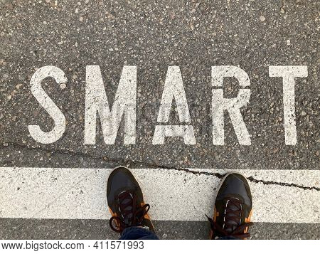 Top View Of Man Standing In Front Of White Smart Word Inscription On Asphalt In Switzerland