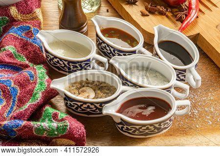 A Set Of Several Different Sauces In Ceramic Saucers. Mushroom Sauce, Adjika, Cheese Sauce, Garlic S