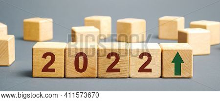 Wooden Blocks With The Inscription 2022 And An Up Arrow. The Forecast Concept For 2021. Business For
