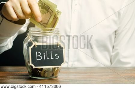 A Man Puts Money In A Glass Jar With The Word Bills. Utility Bill Payment Concept. Housing, Electric