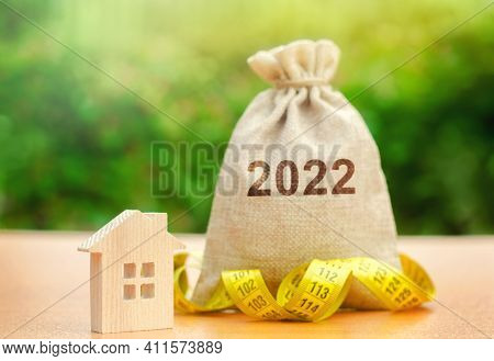 Money Bag 2022 And A Wooden House. Real Estate Concept. Family Budget Planning. Investments, Plans,