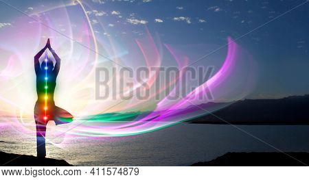 Silhouette of woman sits in a otus pose on beach sunset view, glowing seven all chakra. Kundalini energy. girl practicing yoga meditation outdoors