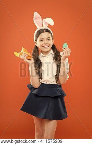 Little Schoolgirl In Rabbit Ears Hold Carrot. Easter Eggs. Happy Easter. Origins Of Easter Tradition