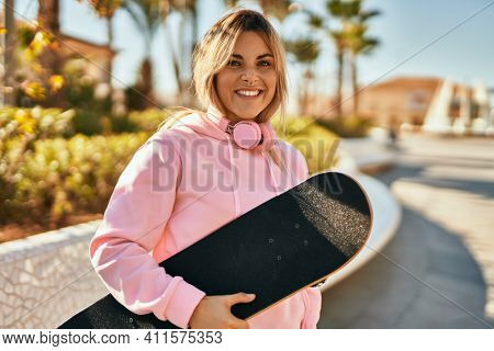 Young blonde skater girl smiling happy holding skate at the city.