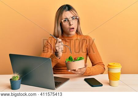 Young caucasian woman working at the office eating healthy salad in shock face, looking skeptical and sarcastic, surprised with open mouth