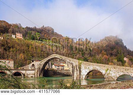 Ponte della Maddalena over the Cercchio River. Medieval bridge with magnificent architecture. Italy. Province of Tuscany. Outskirts of Bagni di Lucca
