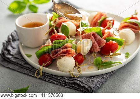 Italian Style Appetizer, Antipasto Skewer Or Caprese On A Stick With Basil, Salami, Mozarella And To