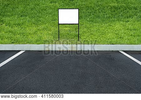 Horizontal Shot Of A Blank Sign At The End Of A Parking Space With Green Grass Behind It.  This Is A