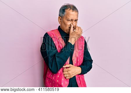 Middle age indian man wearing traditional indian clothes smelling something stinky and disgusting, intolerable smell, holding breath with fingers on nose. bad smell