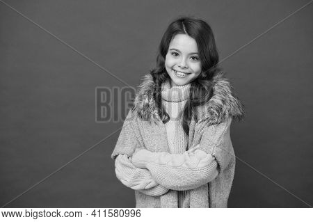Smiling Cute Kid Has Long Curly Hair Wearing Warm Knitted Sweater And Autumn Waistcoat On Red Backgr