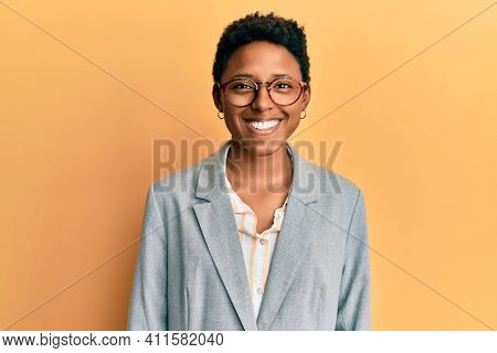 Young african american girl wearing business jacket and glasses with a happy and cool smile on face. lucky person.