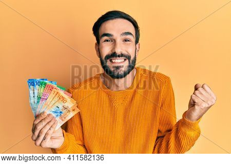Young hispanic man holding swiss franc banknotes screaming proud, celebrating victory and success very excited with raised arm