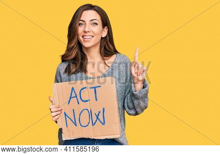 Young brunette woman holding act now banner surprised with an idea or question pointing finger with happy face, number one