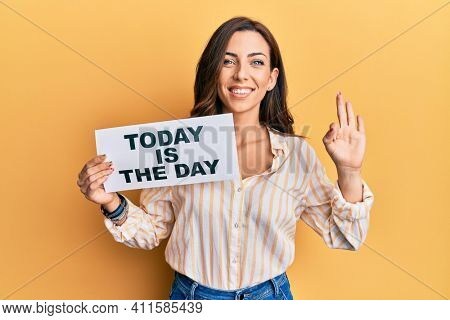 Young brunette woman holding today is the day doing ok sign with fingers, smiling friendly gesturing excellent symbol