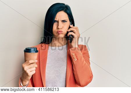 Young caucasian woman having conversation talking on the smartphone holding take away coffee puffing cheeks with funny face. mouth inflated with air, catching air.