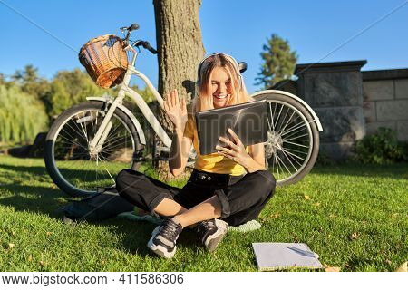 Teenager Student Girl 16, 17 Years Old Sitting On Grass In Park Talking Online Using Video Call On D