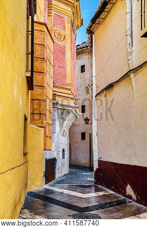 Old medieval narrow street with Spanish style colorful facades of buildings and blue sky in the background. Malaga, Andalucia, Spain