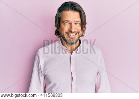 Middle age handsome man wearing business shirt looking positive and happy standing and smiling with a confident smile showing teeth