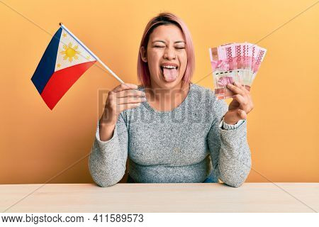 Hispanic woman with pink hair holding philippine flag and philippines pesos banknotes sticking tongue out happy with funny expression.