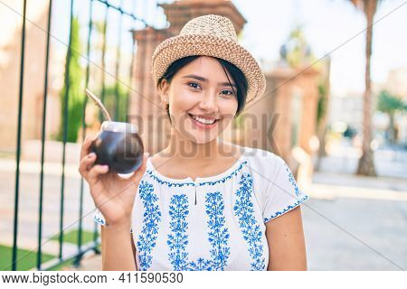 Young latin tourist girl on vacation smiling happy holding cup of mate infusion walking at the city.
