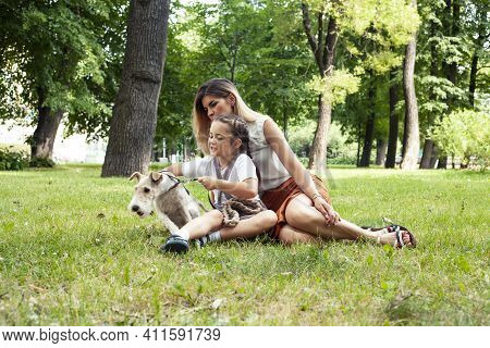 Young Pretty Caucasian Mother Walking With Little Cute Daughter And Dog Fox Terrier, Lifestyle Peopl