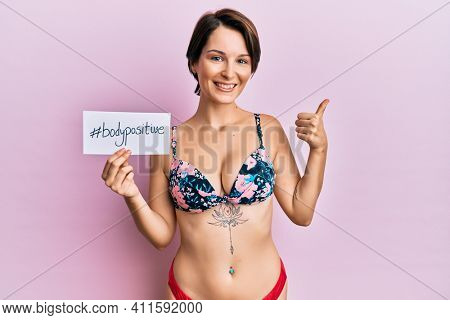 Young brunette woman with short hair wearing bikini holding positive vibes banner smiling happy and positive, thumb up doing excellent and approval sign