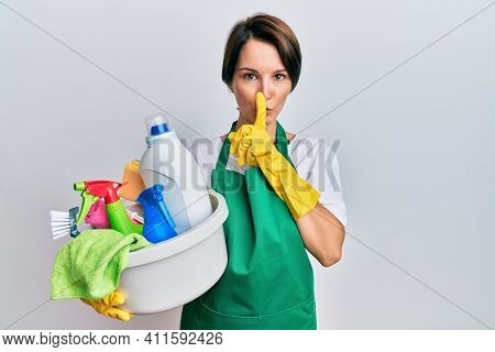 Young brunette woman with short hair wearing apron holding cleaning products asking to be quiet with finger on lips. silence and secret concept.