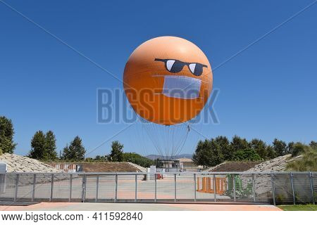 IRVINE, CALIFORNIA - 30 AUG 2020: The Orange County Great Park Balloon ride sports a COVID-19 face mask and sunglasses as it sits at the station.