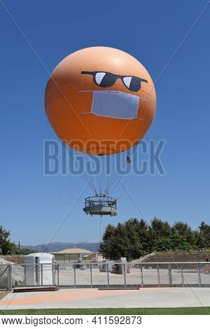 IRVINE, CALIFORNIA - 30 AUG 2020: The Orange County Great Park Balloon lifting off sports a COVID-19 face mask and sunglasses to remind visitors of the need to social distance and cover up.