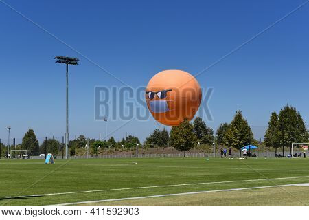 IRVINE, CALIFORNIA - 30 AUG 2020: The Orange County Great Park Balloon ride sports a COVID-19 face mask and sunglasses seen from across a soccer practice field.