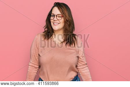 Young plus size woman wearing casual clothes and glasses winking looking at the camera with sexy expression, cheerful and happy face.