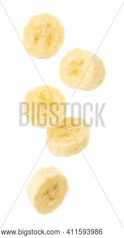 Slices Of Tasty Ripe Banana Falling On White Background