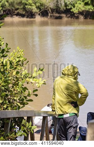 A Fisherman Standing On A Jetty With His Rod Waiting For The Fish To Bite