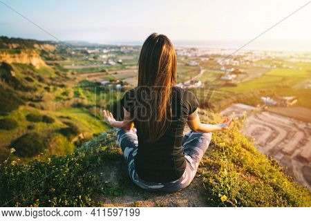 Woman Practices Yoga And Meditates On The Top Of The Mountain With Beautiful View On The City And Oc