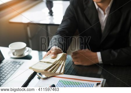 Business Man Sending Money Dollar. During Negotiations On A Desk With A Laptop, Cup Of Coffee And Fi