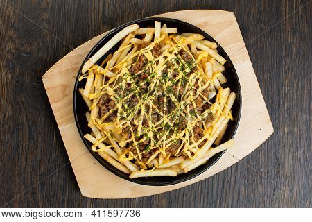 French Fries With Chopped Beef In A Metal Frying Pan On A Wooden Board. Fried Meat Rolls With Cheese