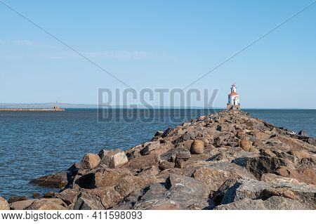 Lighthouse With Red Roof At The End Of A Rocky Pier On Lake Superior, With Calm Water And Clear Blue