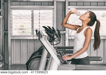 Gym fitness woman drinking water bottle dehydrated during run workout. Healthy Happy girl training on running treadmill machine.