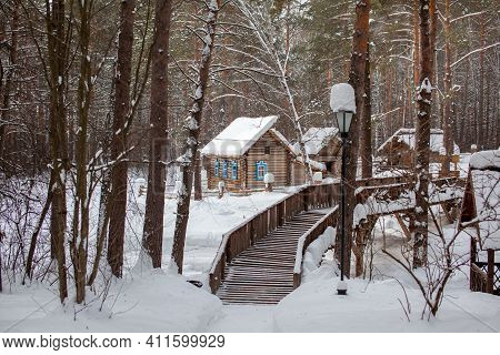 Wooden House With A Farmstead In The Forest In Winter. The House Has Painted Windows. A Wooden Bridg