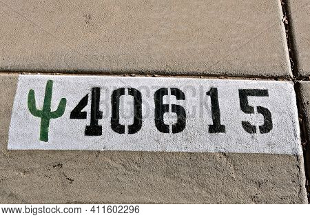 Painted On A Curb Of Southwestern State Is A House Number And Symbolic Cactus Tree.