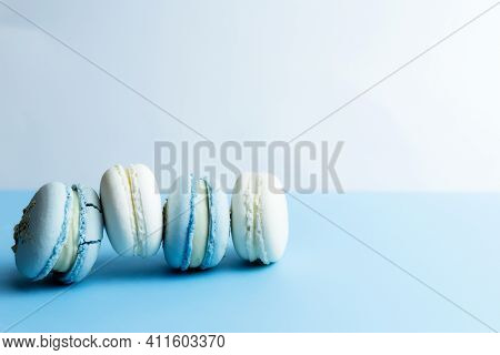 White And Blue Macaroons On The Table, Macaroons On White Blue Background. High Quality Photo